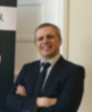 Photograph of Gary McCann wearing a navy suit with shirt and tie. Gary is smiling and has his arms crossed. g with his