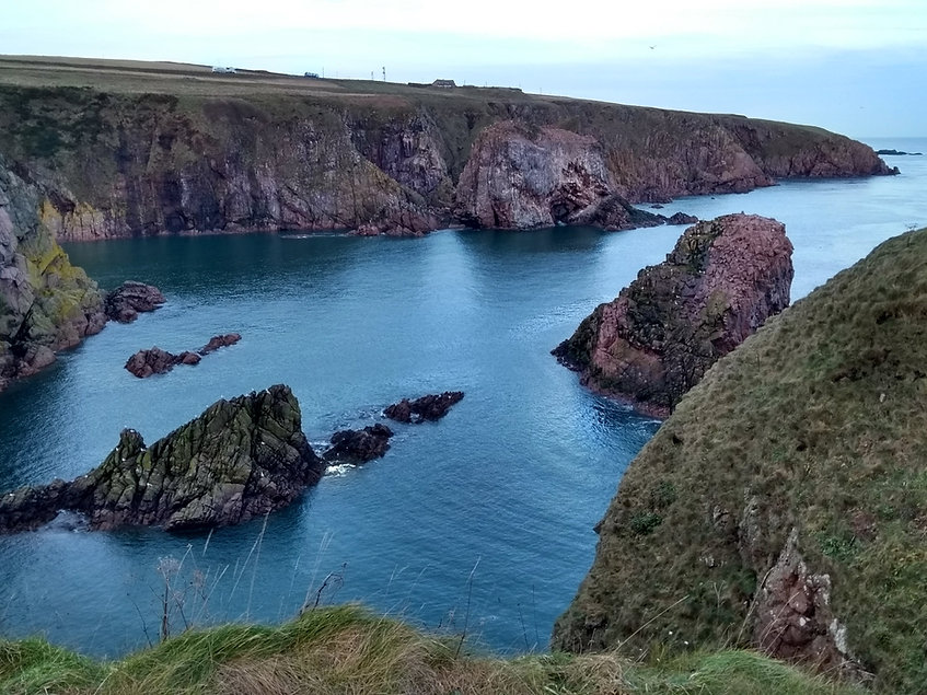 Rugged cliff edges with grey blue water and rocky outcrops.  Sunny day and clear water.