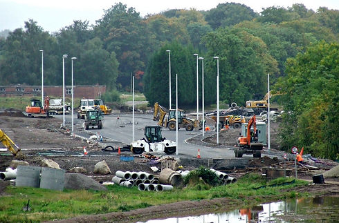 Constuction site at ROF Bishopton with various construction vehicles, pipework, lamposts on new road.  Old red brick former munitions buildings in the background.