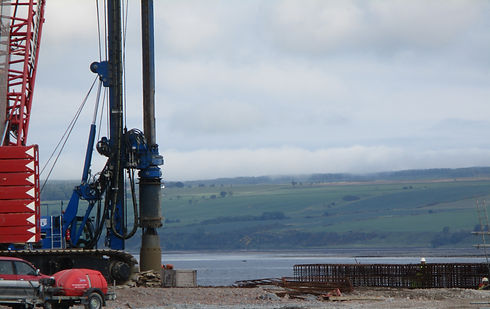 Large piling rig on tracked vehicle on concrete development platform at Phase 4 Cromarty Firth Development with water in the background.