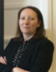 Photograph of Alison McKay wearing a black suit jacket and patterned black and white blouse. Alison is smiling and has her arms crossed.
