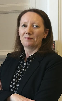 Alison McKay in office smiling with arms crossed.  Alison is wearing a black suit with blouse.