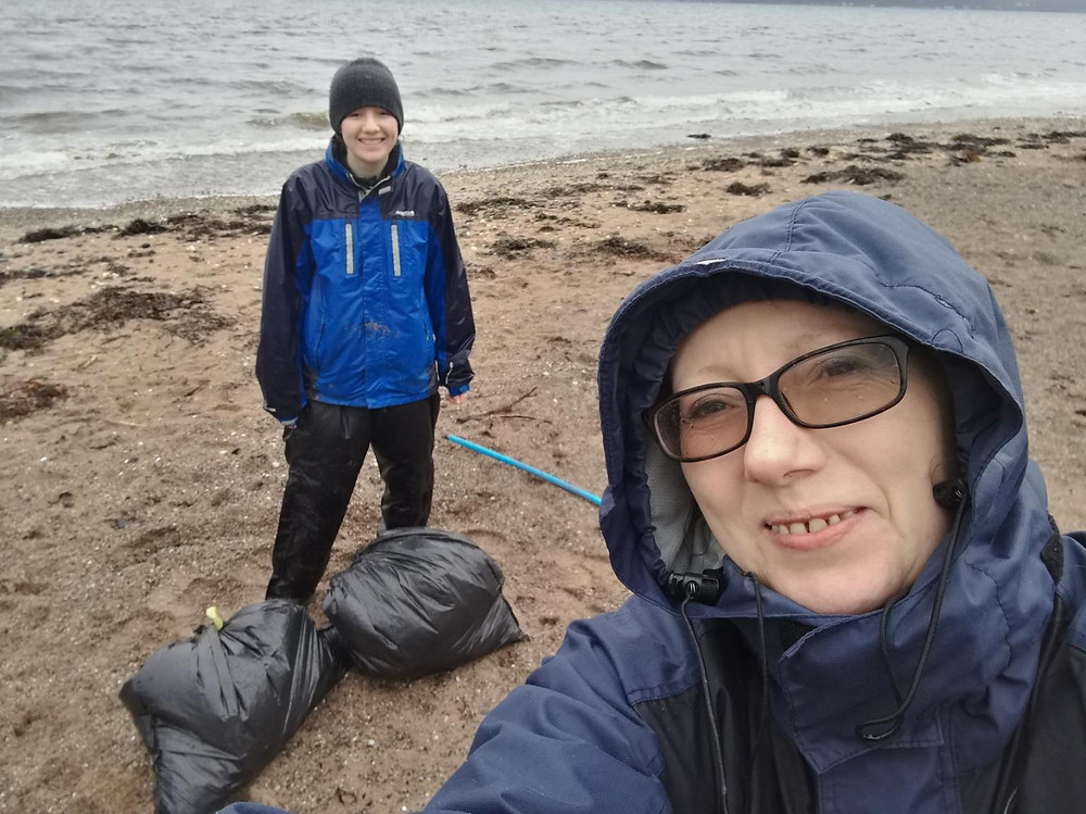Alison McKay and Mhairi McCann of Youth STEM 2030 wearing rain jackets and trousers on Inverkip Beach. Beach is sand and shingle and has bags of litter collected during beach clean. Alison and Mhairi are smiling.It is a cold and grey day.