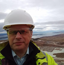 Headshot of Gary McCann with super quarry in the background.  Gary is smiling and wearing a white hardhat, high visibility yellow jacket and safety glasses.