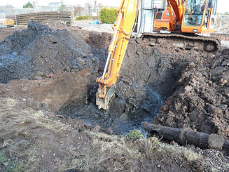 Long reach excavator digging soil with contamination.