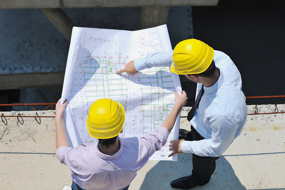 Two engineers wearing yellow hardhats looking and pointing at a large format engineering drawing.