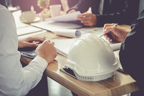 Meeting around a table with notebooks and hardhat