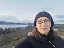 headshot of Alison McKay with view over Clyde Estuary in the background. Alison is wearing a grey wollen hat and black insulated jacket.