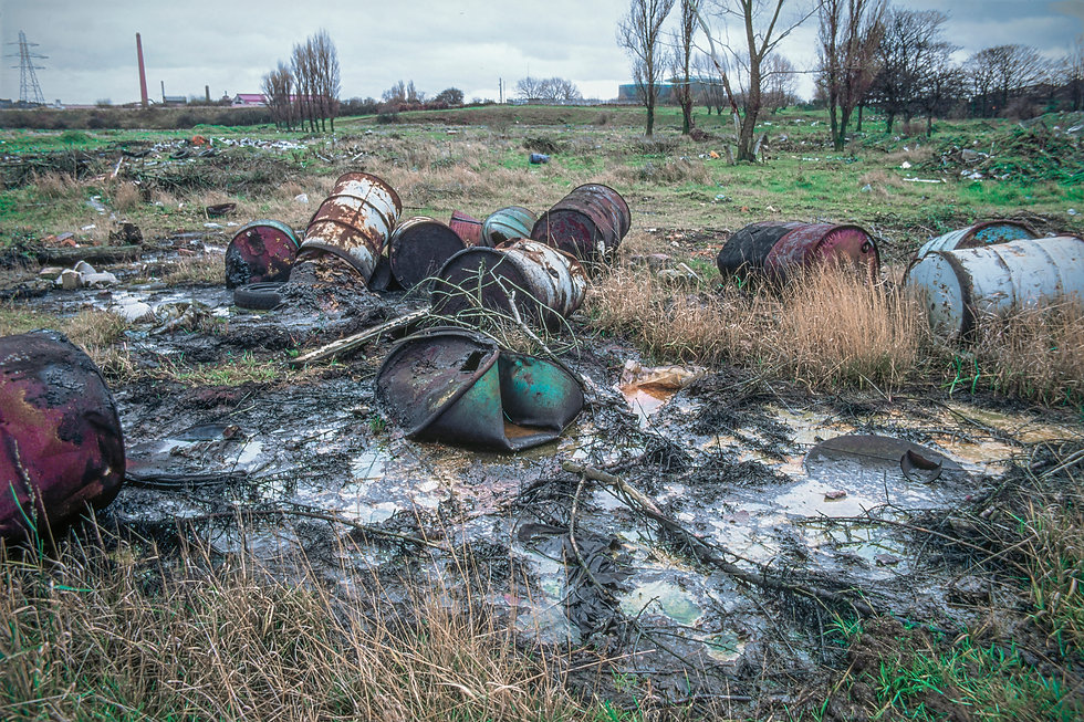 Derelict land with rusty 205 litre chemical containers.  Obvious land contamination and pollution.