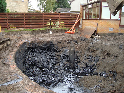 Excavation in residential back garden showing gas works waste contamination. Air monitoring station in background as well as fenceline and conservatory.