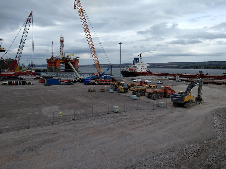 Development platform or berth on quayside with Cromary Firth in background and lots of construction vehicles parked in site compound.  Fenced area with industrial bulk containers.
