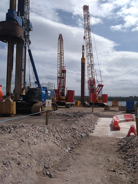 Construction site at Invergordon with large machinery including piling rig. Concrete platform in foreground with Cromarty Firth in background.