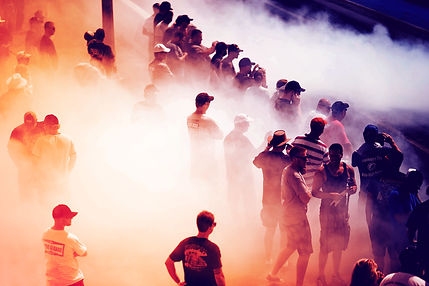 Spectators by a racetrack, surrounded in smoke
