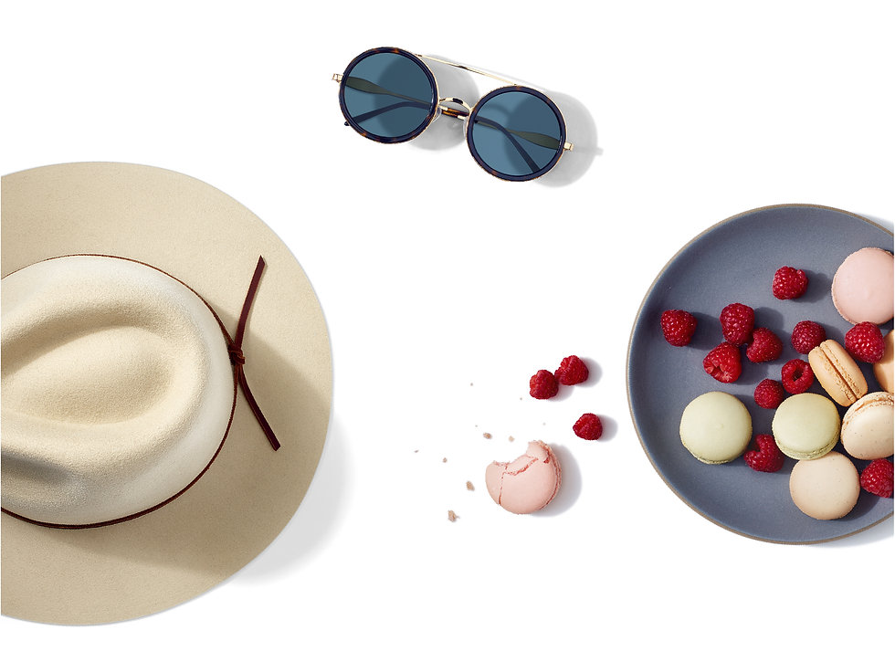 Objects captured from above: sunglasses, wide-brimmed hat, a plate of raspberries and macarons