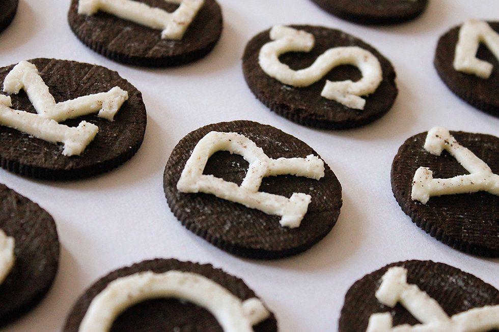 Close up photo of several oreos, showing different letters of the alphabet cut from the cream