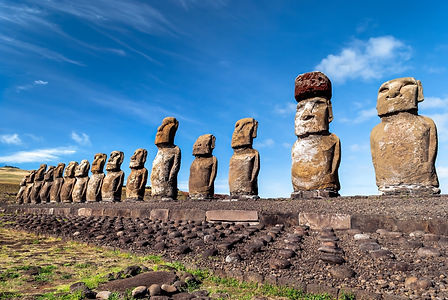 An image of a long row of stone statues all facing the sky
