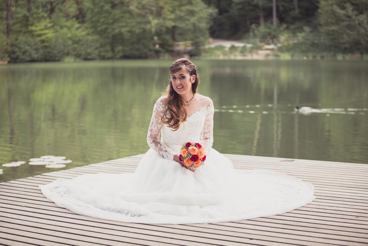 Brautpaarshooting. Braut sitzt auf dem Steg.