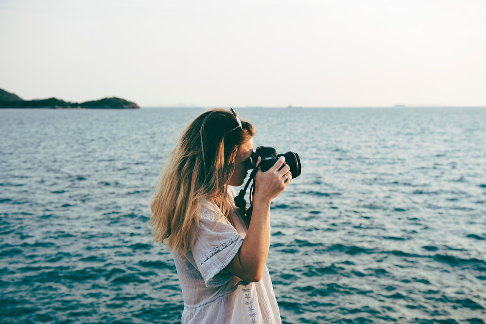 A portrait of the wedding photographer in the front of the sea