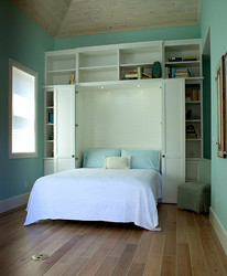 painted white murphy bed with two side cabinets and shelving on top