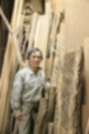 材料となる木の前の三島俊樹さん