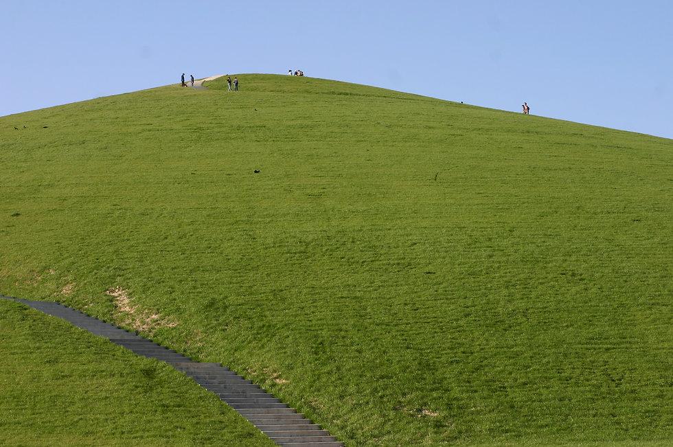 山の斜面、緑の芝生と人、空