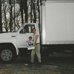 JIM W BABIES IN FRONT OF TRUCK FAR VIEW.