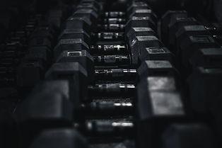 black-dumbbells-in-crossfit-gym-JHMU5GJ.