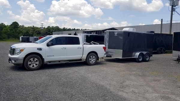 White Nissan Titan hitched to a charcoal gray Diamond Cargo Trailer. Location is at Diamond Cargo Mfg. Plant