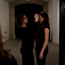 "Caroline Silas (Tunnel Girl) inscribes the designation on fellow ""Tunnel Girl,"" Yoni Tyson."