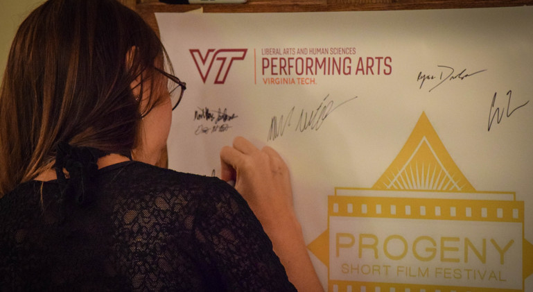 Aline Souza (Myw Speaking to the Night) signs the official Progeny poster in the main lobby of The Lyric Theatre.