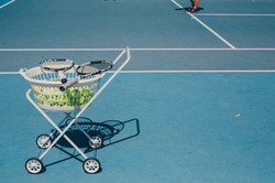 tennis rackets on basket with balls