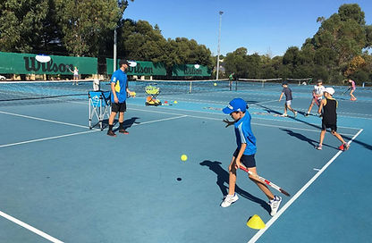kids learning tennis on court with coach