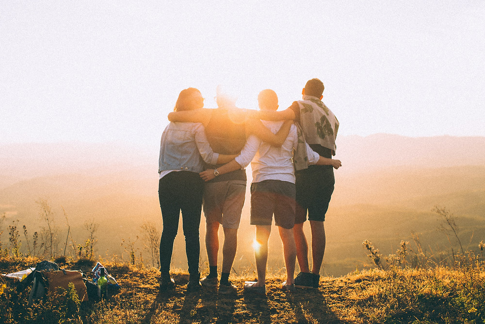 A group of friends with their arms around each other over looking a cliff.  A sunset in the background.