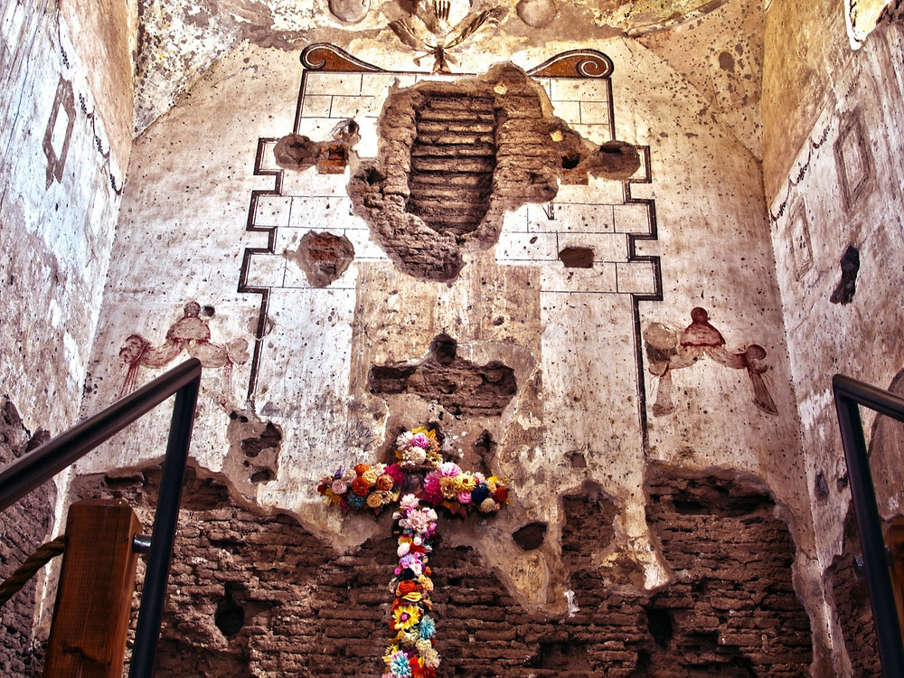 A photograph of the inside of the Tumacacori Mission.  A cross covered in floors is up against the wall.  The mission is showing signs of age with missing pieces of mission walls exposing the brick below.