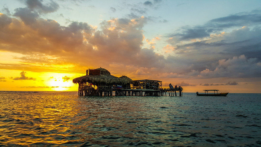The Pelican Bar.  A Bar in a stilt hun in the middle of the ocean.  A sunset is behind the bar with a boat near the bar.