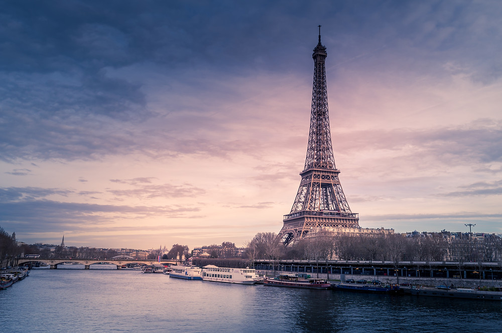 A sunset photo with deep purples of the Eiffel Tower over looking the Seine River. There are river cruise ships in the Seine with a bride leading to the Eiffel Tower.