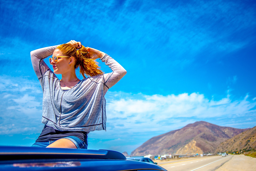 Woman sitting on the seat of a convertible with a backdrop fo the Pacific Coast Highway.