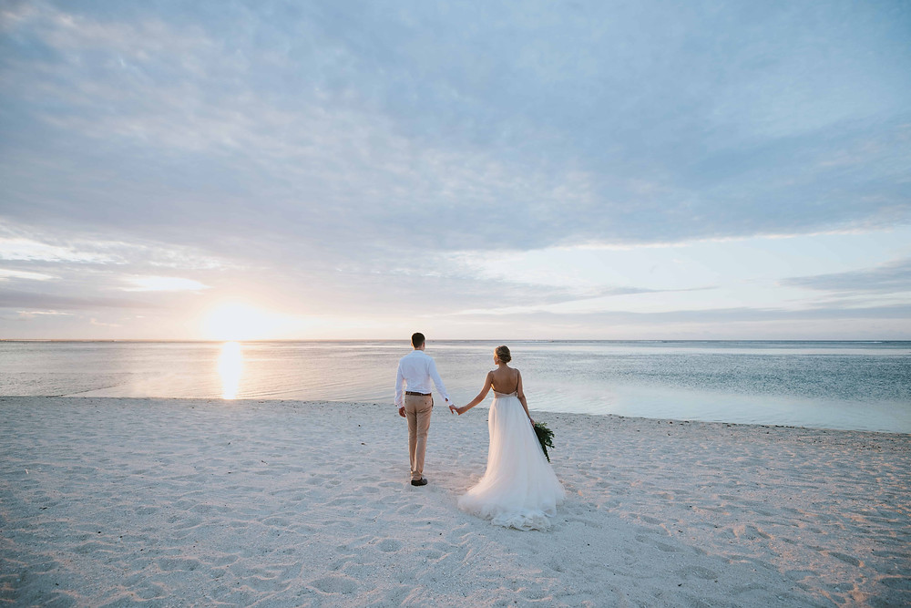 A couple getting married on the beach at sunset.