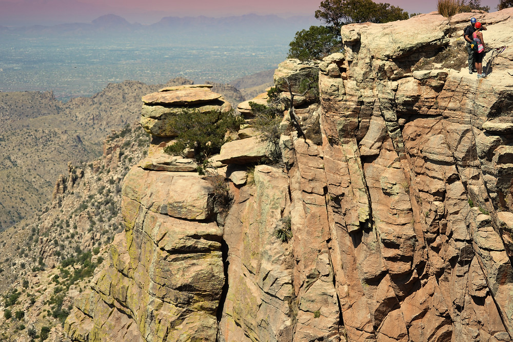 A photo of a cliff on Mt Lemmon in Tucson, AZ the dusky city is in the background.  Two mountain climbs are preparing to climb down the cliff face.