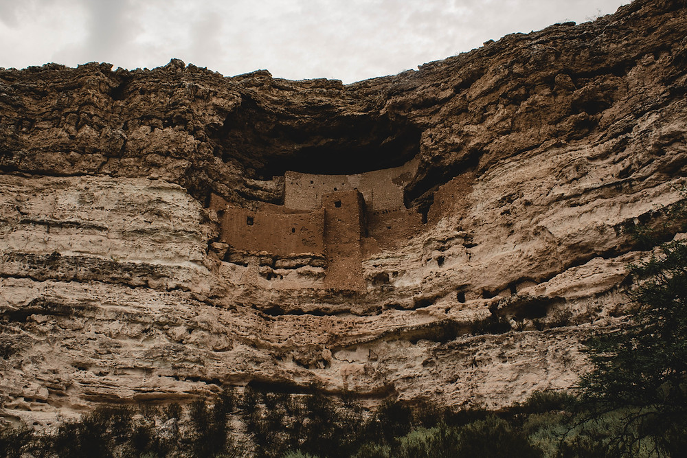 A photo of Montezuma Castle on a cloud day.  The castle is built right into the side of a mountain.