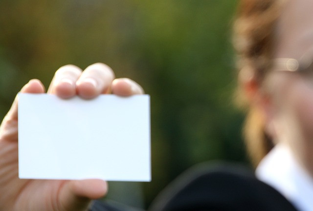 A woman's hand holding a blank business card, with a blurred partial image of the woman in the background.