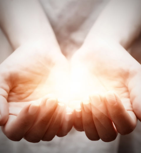 The light in young woman hands in cupped