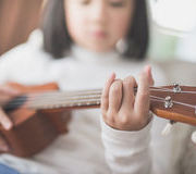 child-playing-ukulele-asian-room-86559731.jpg