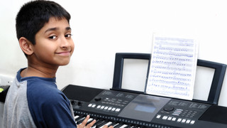 An handsome Indian boy learning music wi
