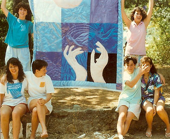 6 girls showing a satin quilt they made