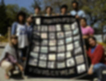 Nine young adults stand around a quilt which they helped artist Nancy Katz make in 1986.