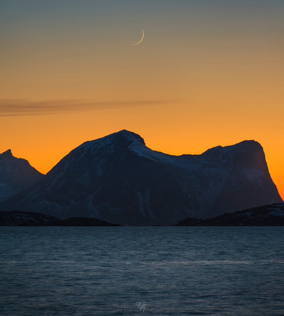 Thin crescent setting over the fjord