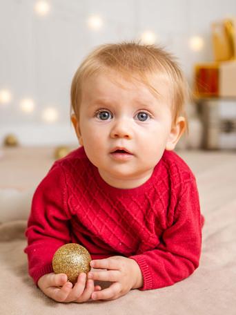 Fotografías de Sesión de Navidad, bebe con sweater rojo de navidad, bebe rubia de ojos claros sonriendo posando, Fotografías de Sesión de Navidad, Christmas Photo Session, Luces de Navidad en decorado dorado de navidad