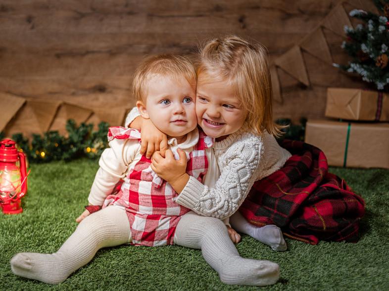 Fotografías de Sesión de Navidad, Niña abrazando a bebe, hermanas, sisters, blonde sisters, niñas en Columpio navideño, Fotografías de Sesión de Navidad, Christmas Photo Session,