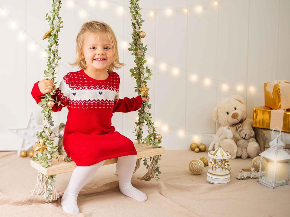 Navidad, niña con sweater rojo en columpio navideo, niña rubia de ojos claros sonriendo posando, Fotografías de Sesión de Navidad, Christmas Photo Session, Luces de Navidad en decorado dorado de navidad